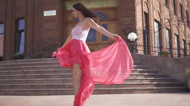 das glamouröse Mädchen im Abendkleid hat Spaß und Schwindel auf der Straße. Tuch flattert im Wind.