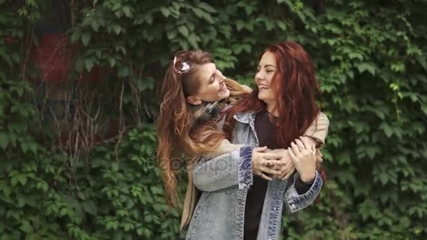 Girlfriends embrace. female friendship. Red-haired girl hugs her best friend from the back. Laughter and fun. 20s