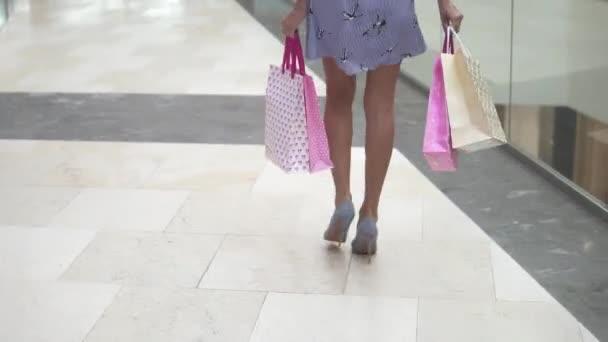 nohy dívky close-up shopaholic. šťastný a spokojený mladá žena s nákupní tašky pro obchodní centrum. Dobré obchody