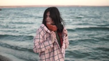 Portrait of a beautiful young woman on the beach. girl in autumn coat outdoors