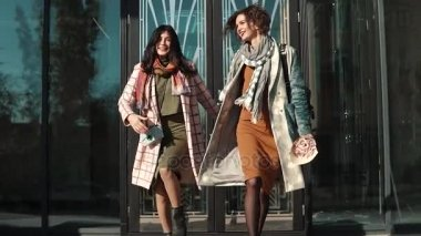 Two young women goofing around and having fun walking on the street. Friends spend time together. Slow motion
