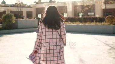 Attractive young woman playfully turns around at the camera. girl in autumn coat with back view. the girl is running from the camera. slow motion