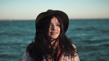 Portrait of cute girl closeup on sea background. young woman in autumn coat and hat posing and smiling at the camera.. Slow motion