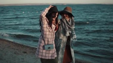 Carefree girlfriend walk along the beach at sunset and enjoy the warm autumn evening. two girls in autumn coat have fun together. slow motion