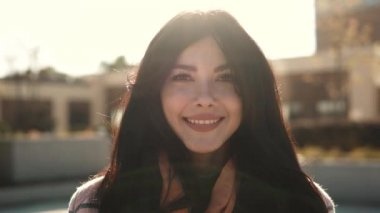 Close-up portrait of a fashionable young woman in the rays of the setting sun. beautiful girl on a city background