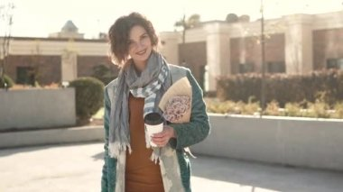 Young woman with a bouquet of flowers and a Cup of coffee posing at camera on the background of urban architecture. fashionable girl in an autumn coat