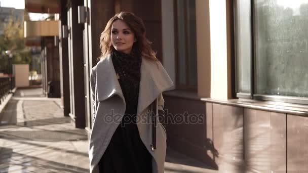 Charmante junge Frau läuft im Mantel durch die Herbststadt und lächelt. Nettes Mädchen vor dem Hintergrund moderner Architektur. Zeitlupe