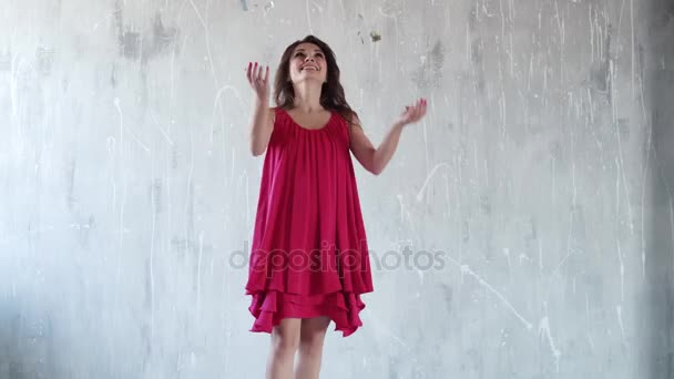 vidám, gondtalan lány dobja fel a cukorka és nevet. lány a bulin. piros ruhás vonzó fiatal nő. a lány, füstös szemek.