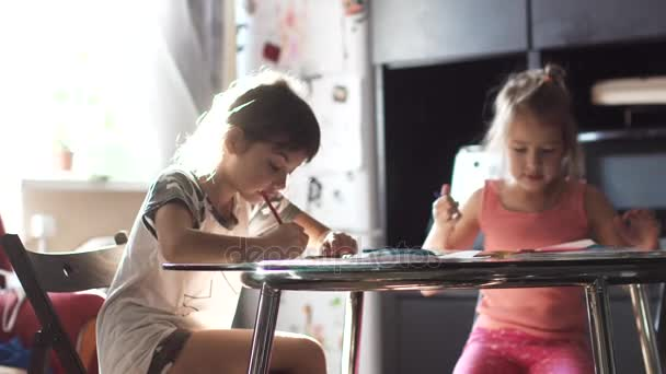 due bambine disegno con i pastelli che si siede al tavolo della ...