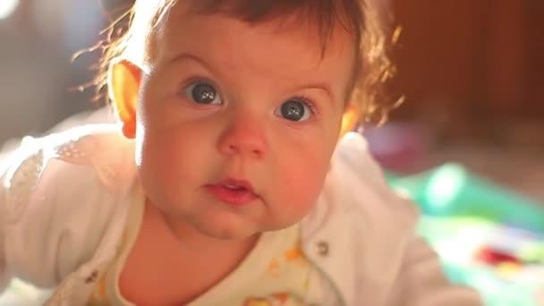 6 měsíc staré dítě leží na posteli a krásně se usmívá. malé modrooké dítě doma