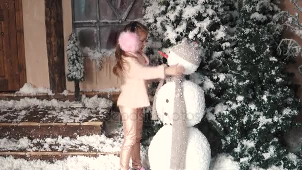 Christmas or new year. a little girl makes a snowman
