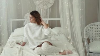 young girl in white sweater and socks sitting on the bed. slow motion