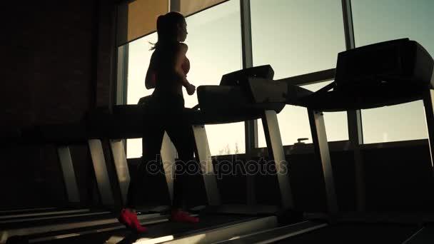 silueta dívky na běžícím pásu. sportovní dívka běží na běžeckém pásu v posilovně. sportovec v sportovní oblečení