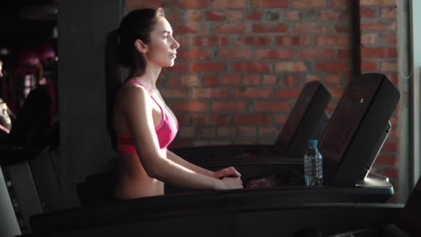 junge Frau läuft auf einem Laufband im Fitnessstudio. Cardio-Übungen in der Turnhalle