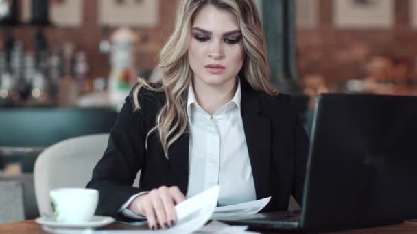 üzleti nő dolgozik a laptop a kávézóban. lány, egy öltöny, a dokumentumok, informális környezetben