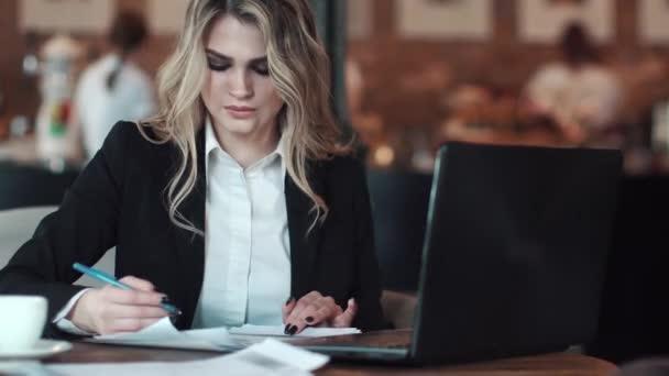 obchodní žena pracuje s dokumenty posezení v útulné kavárně. dívka v podnikání oblek značky dokumentů