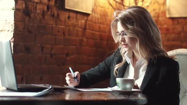 obchodní žena pracující v kavárně na notebooku. dívka v obleku, práci s dokumenty v neformálním prostředí