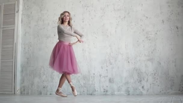 Eine anmutige Ballerina tanzt in rosa Tutu und Spitzenschuhen. Anmutige, leichte Bewegungen. Zeitlupe