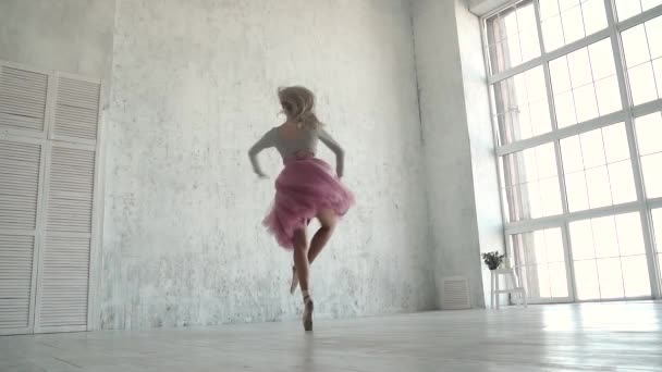 Ballerina performing pirouettes in studio. ballet dancer in a classic tutu and pointe