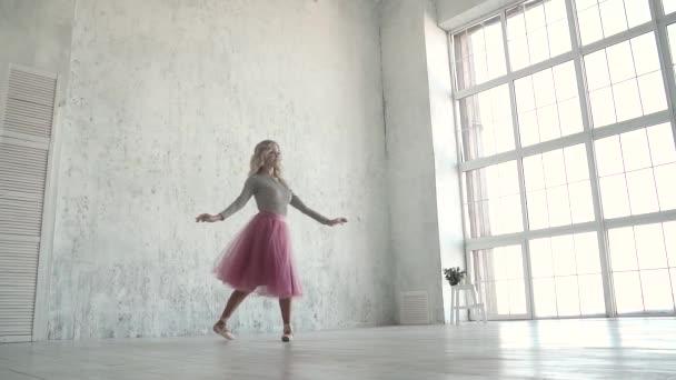 anmutige junge Ballerina, die in einem klassischen Tutu tanzt und vor dem Hintergrund eines großen Fensters spitzt