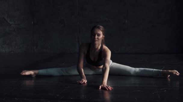 a lány csinál, nyújtás, ül egy string. tornász képzés. Sportruházat-vonzó fiatal nő részt jóga.