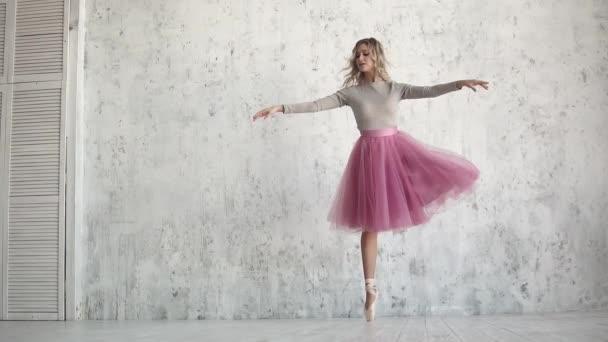Eine elegante junge Ballerina tanzt vor einem riesigen Lichtfenster ein klassisches Ballett. Balletttänzerin in klassischem Tutu und Spitze
