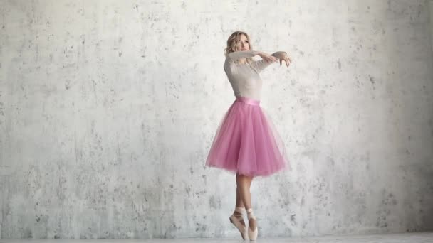 ballerina in the pointe is spinning on tiptoe. ballet dancer in a classical pack on a background of a light wall