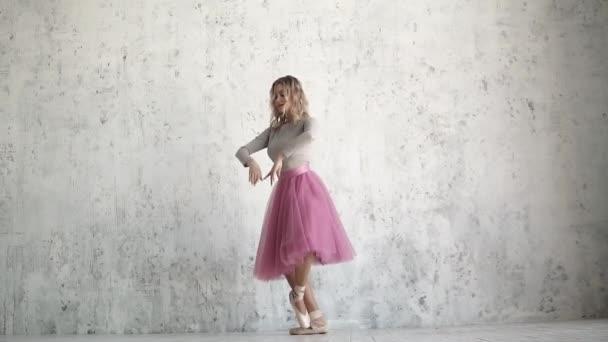 Die junge Ballerina tanzt ein klassisches Ballett. Balletttänzerin in rosa Tutu und goldenen Spitzen