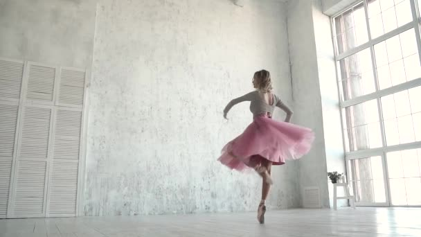 The ballet dancer is spinning in a classic tutu and pointe shoes. A young ballerina dances on tiptoe against the background of a large light window