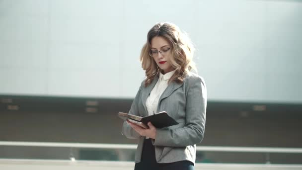 business woman is looking at the notes in her notebook. girl in a gray jacket in the lobby of an office building