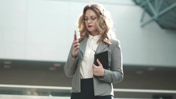 fiatal nő, egy öltöny teszi a hívást a mobiltelefonján. portréja egy üzleti nő egy lobbi egy irodaház
