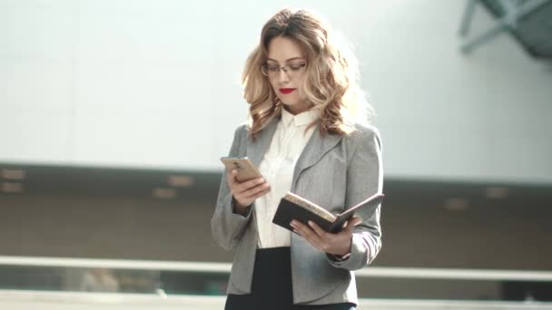 mladá žena v obleku psaní zprávy na mobilním telefonu. portrét ženy obchodní budovy úřadu