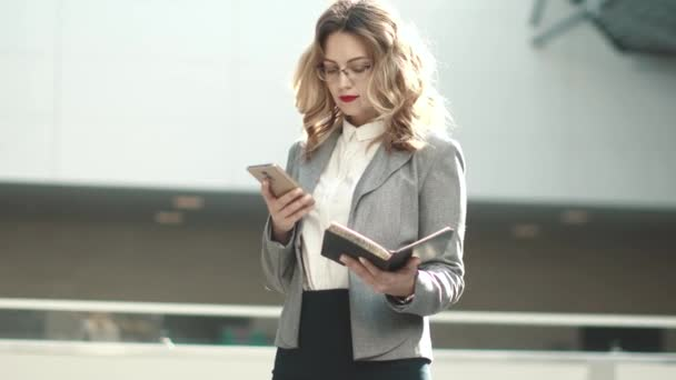 Geschäftsfrau synchronisiert Notizen vom Notizblock auf ihrem Smartphone