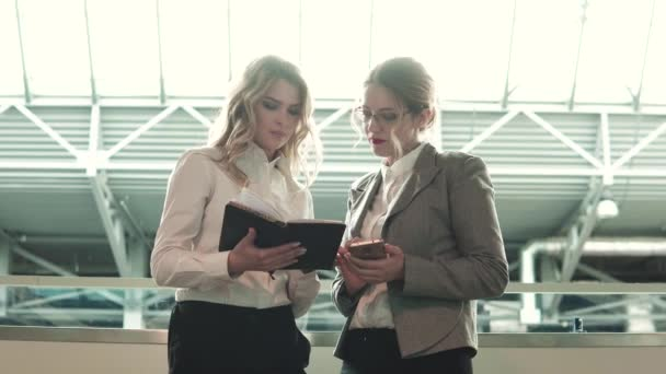 Ein Geschäftstreffen. Zwei Frauen unterhalten sich in der Lobby des Business Centers. Managerin hält Notizbuch in der Hand