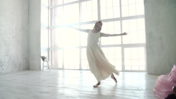 mladí baletku tančící na pozadí velké okno. baletka v lehké šaty a Pointe boty. koncept mládí a krásy. Zpomalený pohyb
