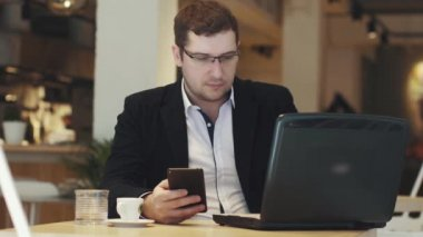 young business man working on laptop and smartphone sitting at table in coffee house