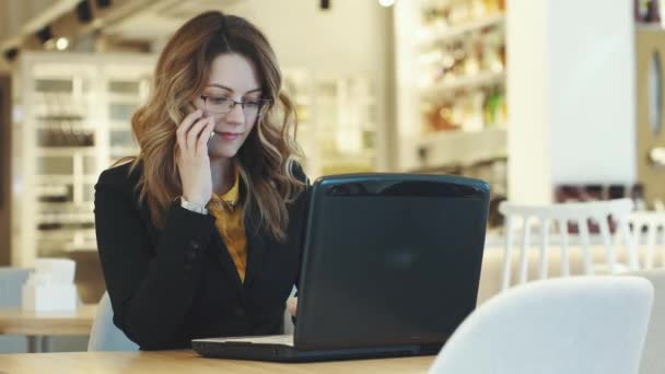 a young business woman works in a cafe and answers a phone call. girl in business suit working on laptop