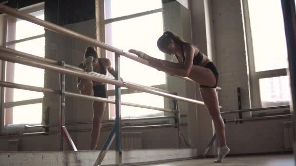 sportovní holka dělá strečink před zrcadlem v tělocvičně. atlet protahuje svaly nohou na břevno
