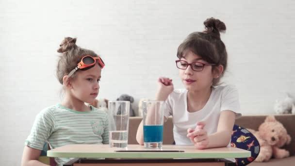 esperimento chimico. i bambini sono impegnati in chimica elementare a casa. la sorella maggiore spiega le basi della scienza per la sorella minore. scienza per bambini