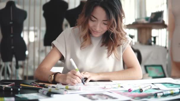 Una mujer asiática joven trabaja en una tienda de ropa. Diseñadora de modas  hace trazos en papel– metraje de stock 2fb055a9a2aa