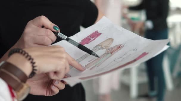 c26e7ea64d9ad Jovem estilista, alfaiate e costureira trabalha com um assistente e olha  para o desenho de