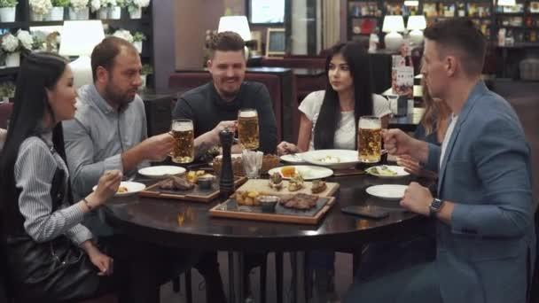 Gruppo multietnico di amici a cena in un caffè. una grande azienda divertirsi insieme, ridere e parlare. gli uomini brindare