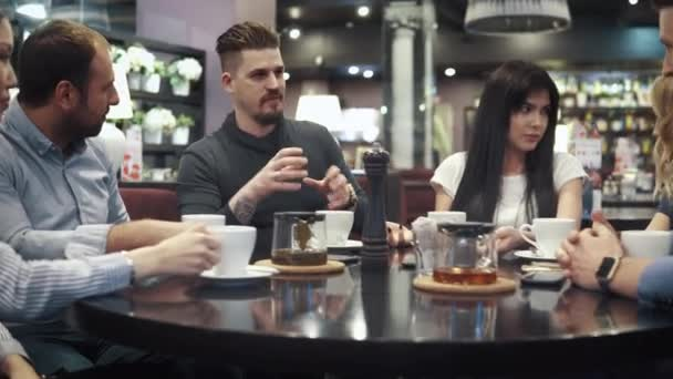 large company of friends at a table in a cafe or restaurant. relaxed communication of friends over dinner