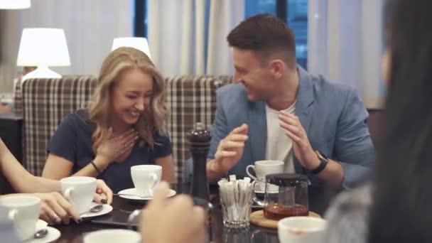 gli amici, ridere e divertirsi seduti ad un tavolo in un ristorante. Una compagnia di amici passa insieme il tempo e gode di socializzazione.