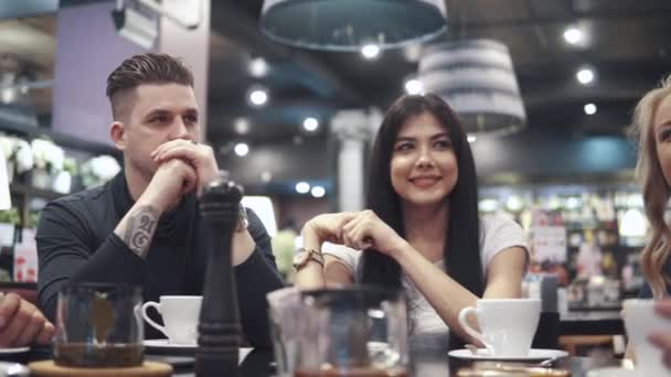 gli amici, ridere e divertirsi seduti ad un tavolo in un ristorante. Una compagnia di amici passa insieme il tempo e gode di socializzazione