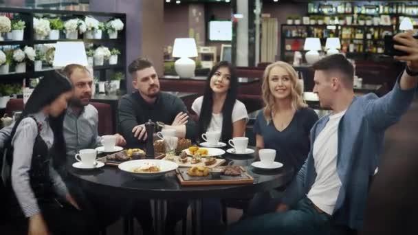 un grande gruppo di amici fa un selfie seduto a un tavolo in un bar o ristorante