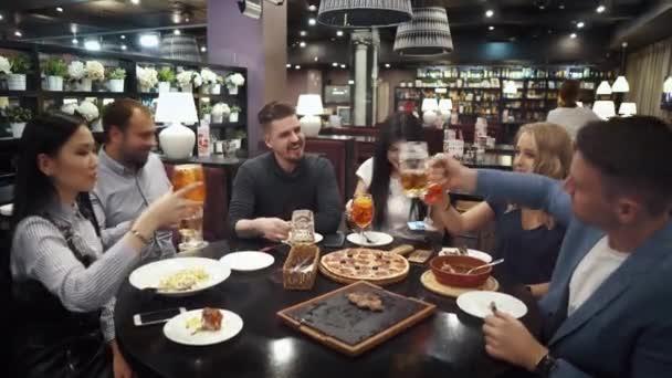 Velká Veselá společnost přátel se sesedli kolem stolu. přátelé poraďte, úsměv a clink brýle