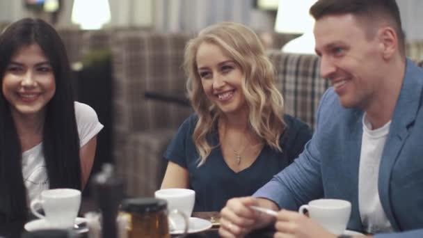 dvě dívky a mladý muž, zatímco sedí u stolu v kavárně nebo v restauraci a smíchu