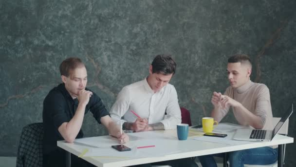 three men discuss a project and plan while sitting at a table in an office