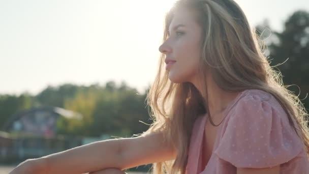 Charmante junge Frau sitzt am Strand im Sand